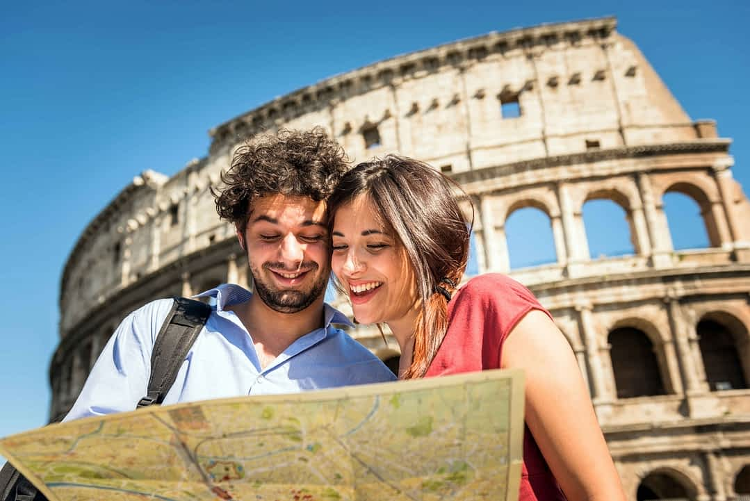 Tourists in front of the Colosseom in Rome reading a city map