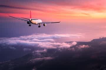 Flugzeug fliegt gen Sonnenuntergang
